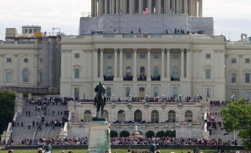 People gather at the US Capitol to watch space shuttle Discovery sitting atop a 747 as it flies over Washington en route to the National Air and Space Museum