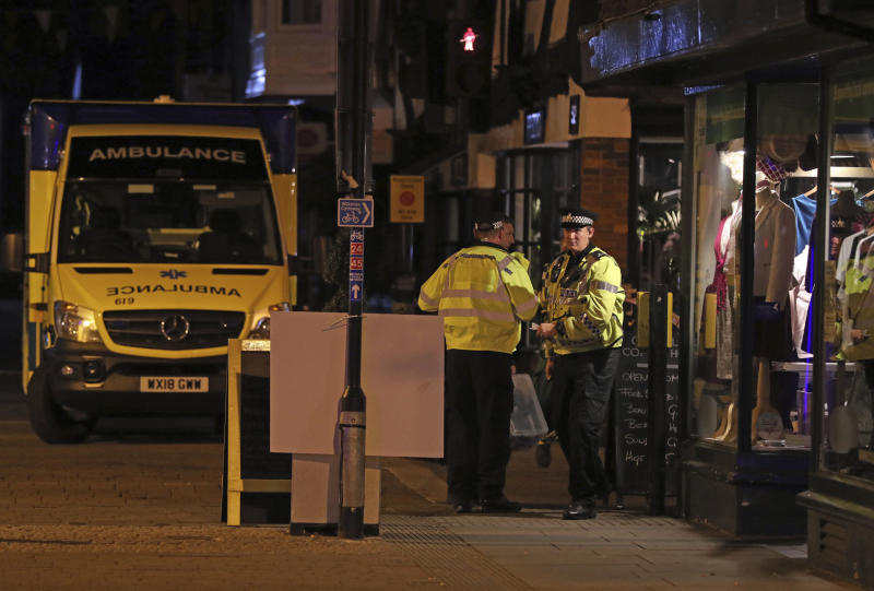 """Emergency services personnel stand near the Prezzo restaurant in Salisbury, Britain, where police closed roads as a """"precautionary measure"""" after two people were taken ill from the restaurant, Sunday Sept. 16, 2018. Police closed roads and called a hazardous response team Sunday night after two people became ill at the restaurant in the English city where a Russian ex-spy and his daughter were poisoned with a chemical nerve agent. The conditions of a man and woman who got sick at the restaurant was under investigation. (Jonathan Brady/PA via AP)"""