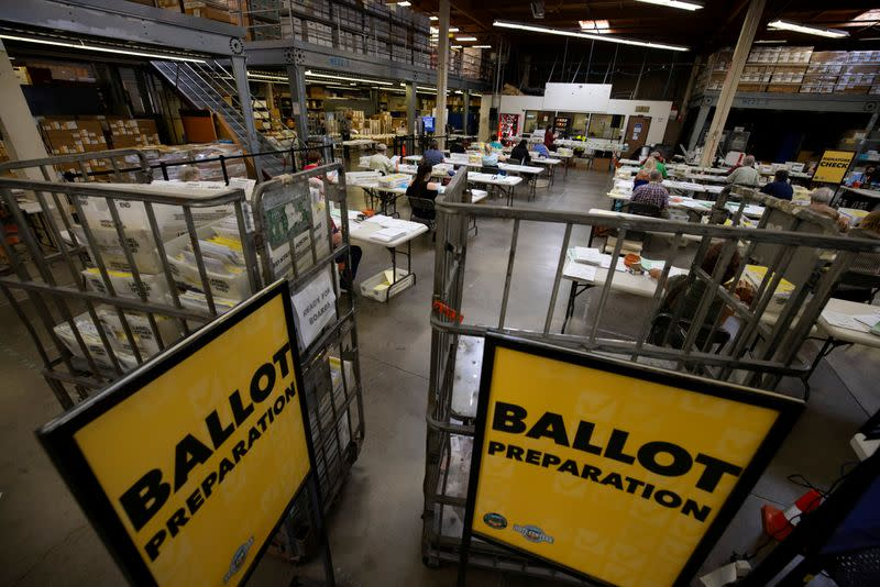 FILE PHOTO: Some of the hundreds of thousands of early mail-in ballots are processed for scanning by election workers at the Orange County Registrar of Voters in Santa Ana, California,