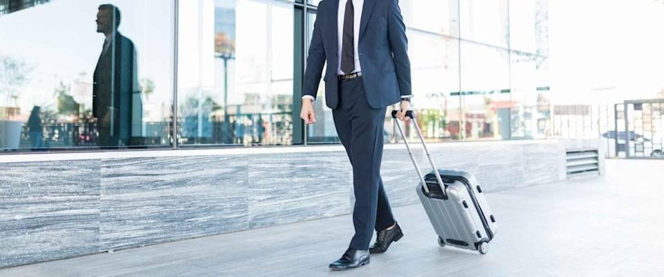 Smiling and good looking manager with suitcase walking outside modern office