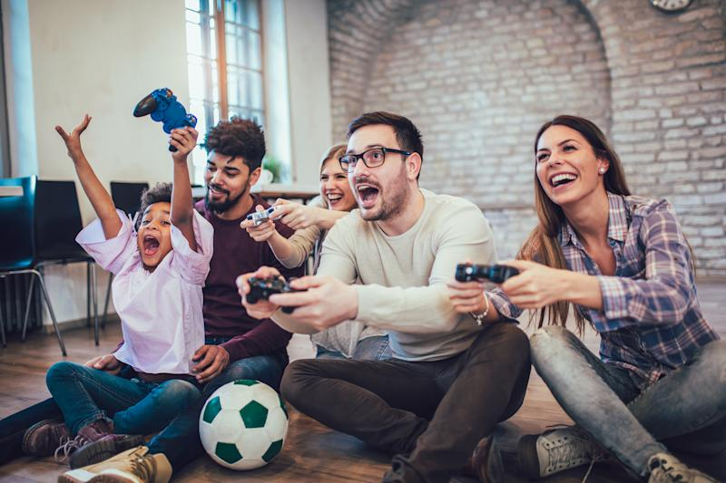 Four adults and a child sitting cross-legged on the floor with gaming consoles in their hands.