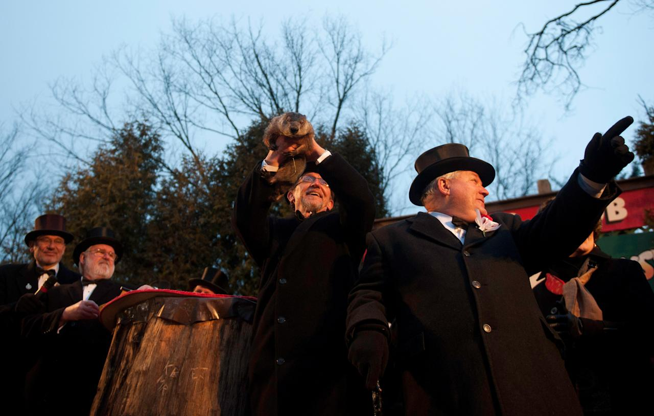 PUNXSUTAWNEY, PA - FEBRUARY 2: Groundhog handler Ron Ploucha holds Punxsutawney Phil after he saw his shadow predicting 6 more weeks of winter during 126th annual Groundhog Day festivities on February 2, 2012 in Punxsutawney, Pennsylvania. Groundhog Day is a popular tradition in the United States and Canada. A smaller than usual crowd this year of less than 15,000 people spent a night of revelry awaiting the sunrise and the groundhog's exit from his winter den. If Punxsutawney Phil sees his shadow he regards it as an omen of six more weeks of bad weather and returns to his den. Early spring arrives if he does not see his shadow, causing Phil to remain above ground. (Photo by Jeff Swensen/Getty Images)