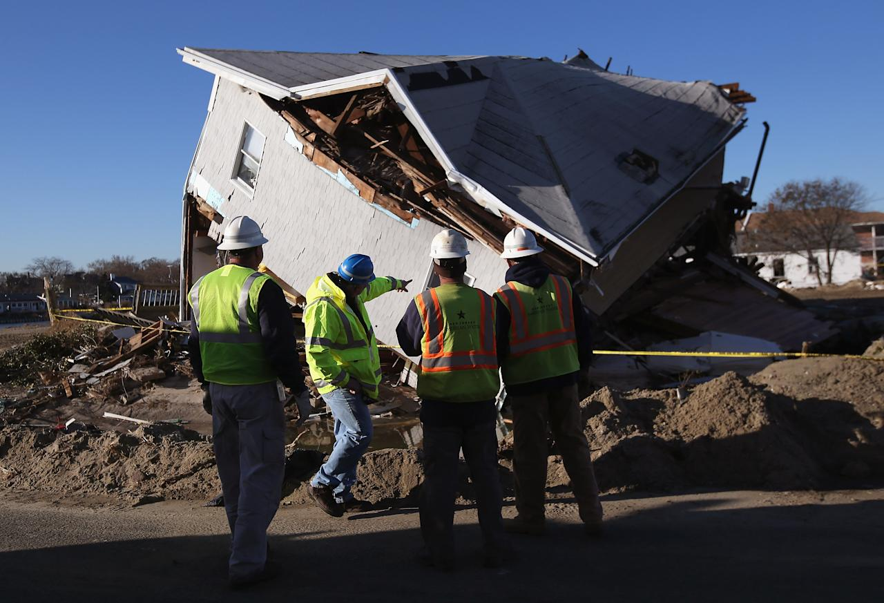 Water workers survery a damaged residence on November 6, 2012 in Sea Bright, New Jersey. Sea Bright was devestated by Superstorm Sandy, and officials allowed residents to come home for a day to salvage valuables from the debris.  (Photo by John Moore/Getty Images)