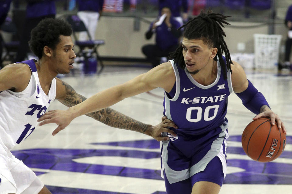 TCU guard Taryn Todd (11) defends against Kansas State guard Mike McGuirl (00) during the second half of an NCAA college basketball game Saturday, Feb. 20, 2021, in Fort Worth, Texas. (AP Photo/Richard W. Rodriguez)