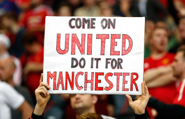 <p>Manchester United fan with a banner in tribute to the victims of the Manchester attack. Reuters / Lee Smith Livepic </p>