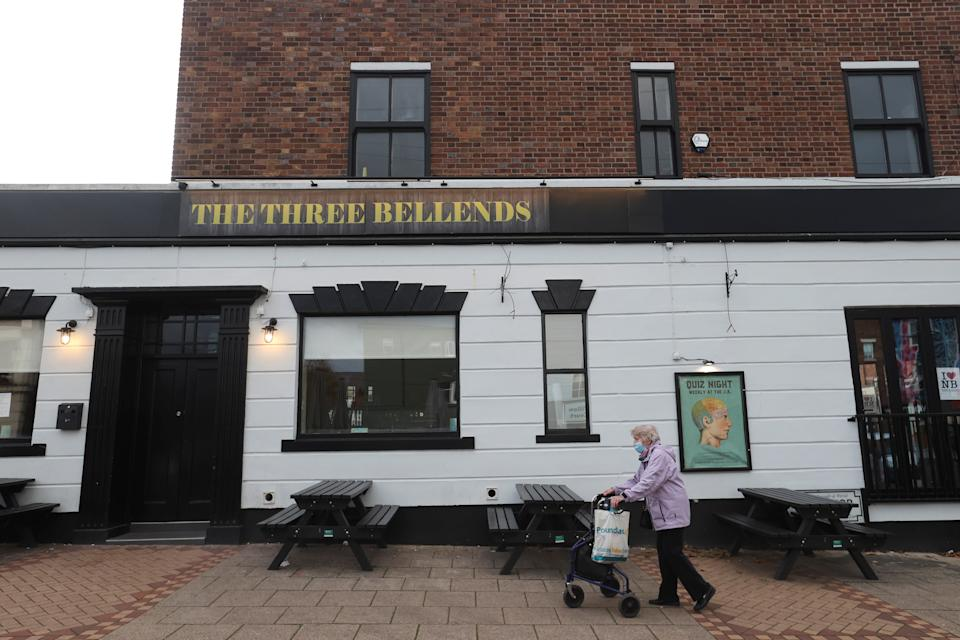 A woman walks past The Three Bellends pub, which depicts images of Boris Johnson, Matt Hancock and Dominick Cummings in its sign, in New Brighton, Britain October 14, 2020. REUTERS/Carl Recine