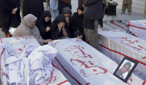 Women from the Shiite Hazara community mourn beside the coffins of coal mine workers, killed by gunmen near the Machh coal field prior to their funeral prayer in Quetta, Pakistan, Saturday, Jan. 9, 2021. Hundreds of Pakistani Shiites gathered to bury 11 coal miners from the minority Hazara community who were killed by the Islamic State group, ending over a week of protests that sought to highlight the minority community's plight. (AP Photo/Arshad Butt)