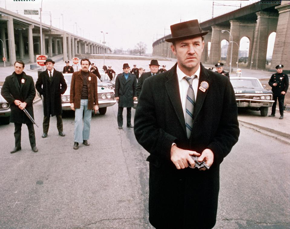 American actor Gene Hackman (foreground), as Detective Jimmy 'Popeye' Doyle, stands in the street by an overpass in front of a group of policemen and holds a gun in his hands in a still from the film 'The French Connection,' directed by William Friedkin, 1971. In the background is actor Roy Scheider (first from left) as Detective Buddy 'Cloudy' Russo and policeman and actor Eddie Egan (1930 - 1995) (fifth from left) as Walt Simonson. (Photo by 20th Century Fox/Hulton Archive/Courtesy of Getty Images)