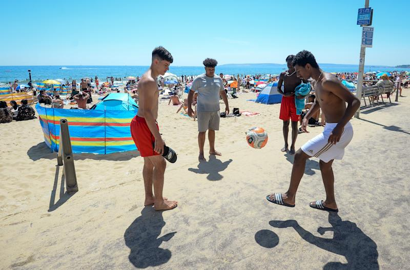 BOURNEMOUTH, ENGLAND - JUNE 25: Young men play football as they enjoy the hot weather on the beach on June 25, 2020 in Bournemouth, United Kingdom. The UK is experiencing a summer heatwave, with temperatures in many parts of the country expected to rise above 30C and weather warnings in place for thunderstorms at the end of the week. (Photo by Finnbarr Webster/Getty Images)