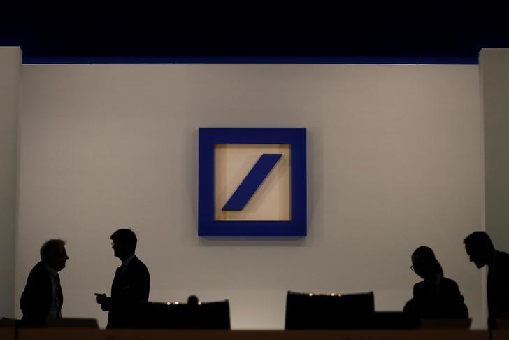 FILE PHOTO - People are silhouetted next to the Deutsche Bank's logo prior to the bank's annual meeting in Frankfurt