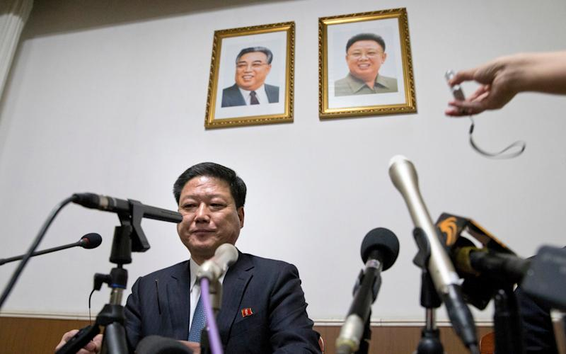 Pak Myong Ho, minister of the North Korean Embassy in China, sits under portraits of the late North Korean leaders Kim Il Sung, left, and Kim Jong Il - Credit: AP
