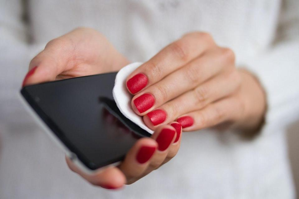 Female hands holding a mobile phone and wipe the screen cloth
