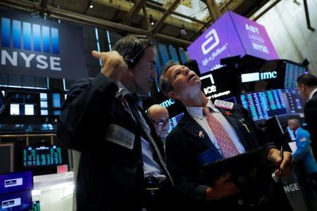 Traders work on the trading floor at the New York Stock Exchange (NYSE) at the opening of the market in New York City