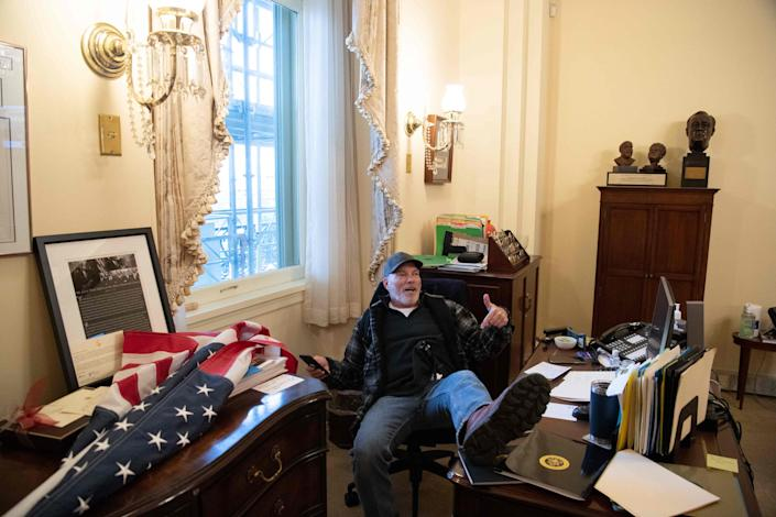 Richard Barnett, a supporter of US President Donald Trump sits inside the office of U.S. Speaker of the House Nancy Pelosi during a riot inside the U.S. Capitol in Washington, DC, January 6, 2021. Authorities arrested Barnett on Friday.
