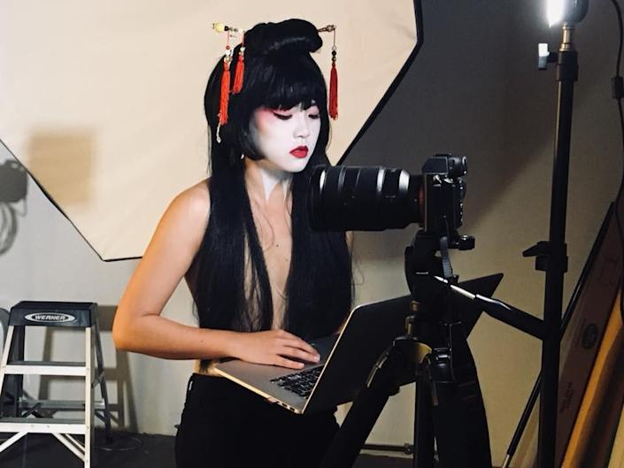 """Kyoko Takenaka working on a laptop behind the scenes of the short film """"Home."""""""