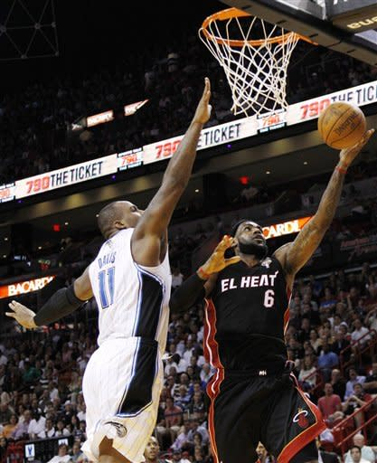 Miami Heat's LeBron James (6) shoots past Orlando Magic's Glen Davis (11) during the first half of an NBA basketball game, Sunday, March 18, 2012, in Miami. (AP Photo/Lynne Sladky)