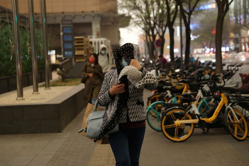 Woman shields herself from wind and rain amid a duststorm in Beijing