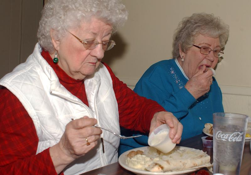 In this Dec. 20, 2012 photo, Marian Rasmussen, left, and Dorothy Gunderson dine on lutefisk at the VFW in Litchfield, Minn. Dozens of Minnesota Scandinavians and the people who love them still flock to the VFW Club in Litchfield every Thursday from November through January, where a $20 bill will get you a big steaming hunk of the frequently mocked fish dish known as lutefisk. (AP Photo/Ron Adams)