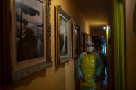 Nurse Isabel Solis, 46, wearing a converted garbage bag apron for protection, walks along a corridor lined with paintings made by Enrique Pastor, 86, during a home visit in Barcelona, Spain, April 1, 2020. Pastor's full-time caregiver tested positive for the virus, leaving his wife to care for the bedridden Pastor without knowing if either of them has COVID-19. (AP Photo/Emilio Morenatti)