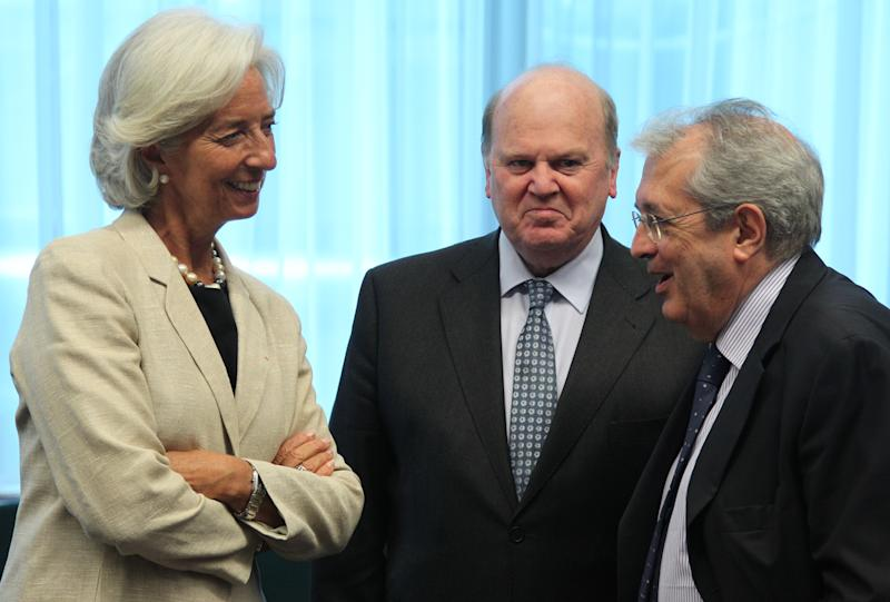 Italian Finance Minister Fabrizio Saccomanni, right, talks with International Monetary Fund managing director Christine Lagarde, left, and Irish Finance Minister Michael Noonan, during the Eurogroup meeting, at the European Council building in Brussels, Monday, July 8, 2013. The finance ministers of the 17 European countries that use the euro are expected to approve the release of another installment of the rescue funds that Greece has been relying on since May 2010. (AP Photo/Yves Logghe)