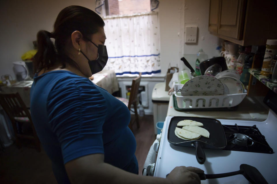 Candida Uraga prepares a meal in the kitchen of her apartment in New York on Friday, March 19, 2021. She has struggled to pay rent after being laid off from her job as a teaching assistant during the pandemic and was denied help under a federally-funded rental assistance program. (AP Photo/Robert Bumsted)