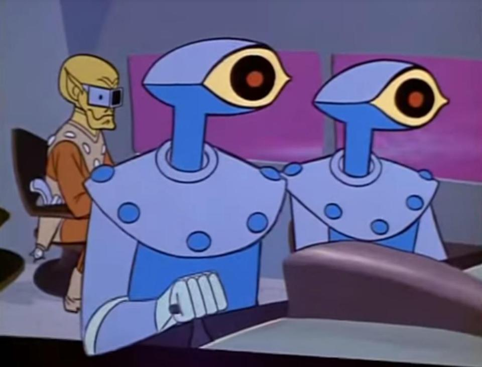 Two one-eyed robots fly a ship with a green, bald-headed alien in the background.