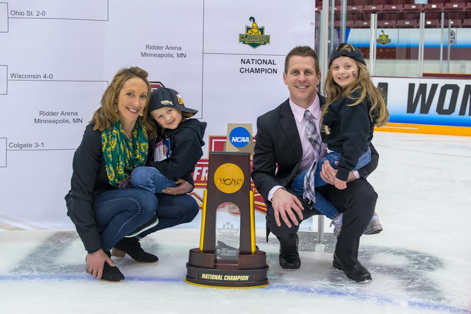 Shannon Desrosiers, husband Matt Desrosiers and their two children pose with Clarkson's national championship trophy. (Provided by Desrosiers)