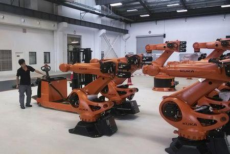 A staff member stands next to robots at a plant of Kuka Robotics in Shanghai in this  August 13, 2014 file photo. REUTERS/Pete Sweeney
