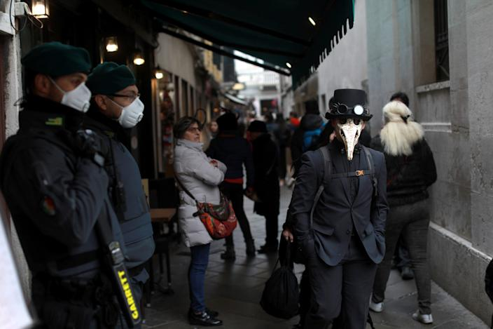 Security personell wearing protective masks stand next to carnival revellers at Venice Carnival, which the last two days of, as well as Sunday night's festivities, have been cancelled because of an outbreak of coronavirus, in Venice, Italy February 23, 2020.