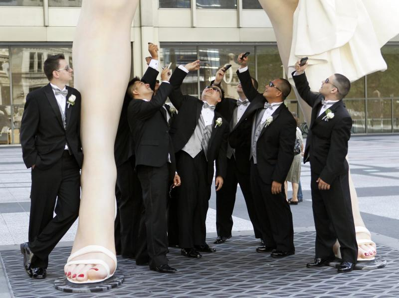 ADDS WEDDING PARTY - Male members of the Hugh and Anya Nguyen wedding party pose under Seward Johnson's 26-foot-tall sculpture of Marilyn Monroe, in her most famous wind-blown pose, on Michigan Ave.  Friday, July 15, 2011 in Chicago. (AP Photo/Charles Rex Arbogast)