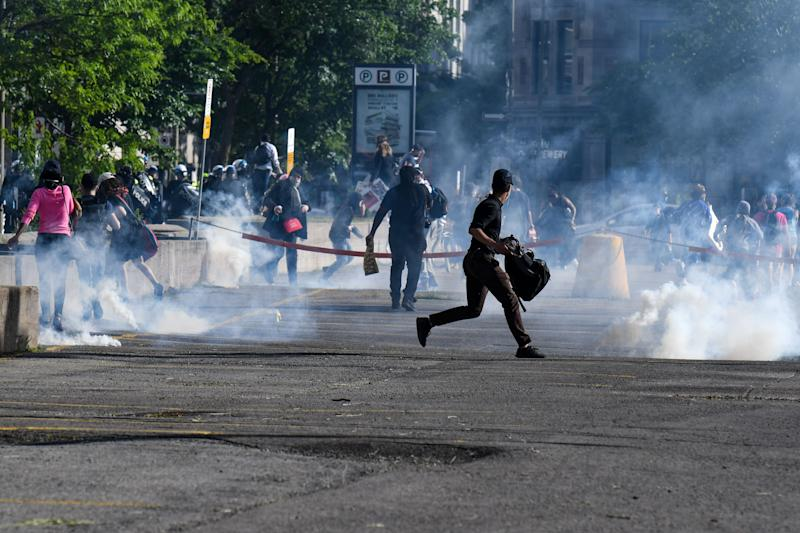 Demonstrators are running as Montreal Police uses tear gas during a march against police brutality and racism in Montreal, Canada, on June 7, 2020.  (Photo: MARTIN OUELLET-DIOTTE/AFP via Getty Images)