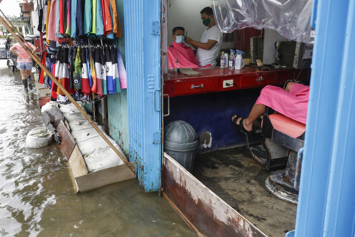 A man has his hair cut at a barbershop flooded by Typhoon Molave in Pampanga province, northern Philippines on Monday, Oct. 26, 2020. The fast moving typhoon has forced thousands of villagers to flee to safety in provinces. (AP Photo/Aaron Favila)