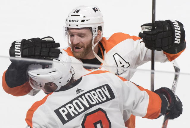 Philadelphia Flyers' Ivan Provorov (9) celebrates with teammate Sean Couturier (14) after scoring against the Montreal Canadiens during overtime NHL hockey action in Montreal, Saturday, Nov. 30, 2019. (Graham Hughes/The Canadian Press via AP)