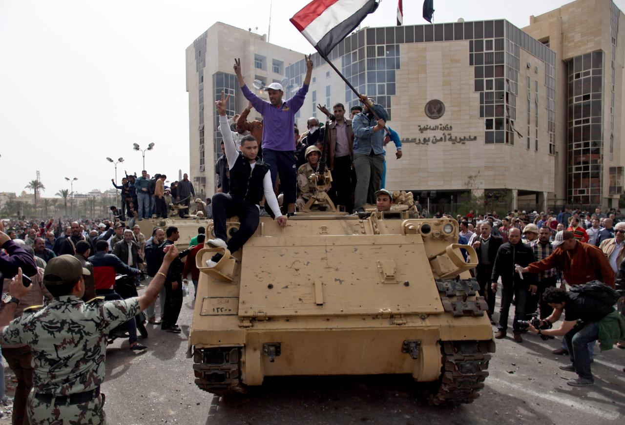 Egyptians chant slogans on top of Egyptian army vehicle as the army is takes over control of the state security building after several days of clashes between protesters and riot police in Port Said, Egypt, Friday, March 8, 2013. (AP Photo/Khalil Hamra)