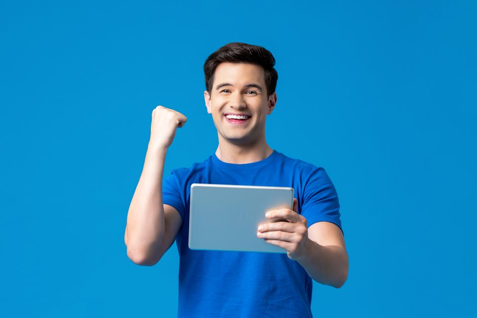 Portrait of excited man holding tablet computer standing against blue background.