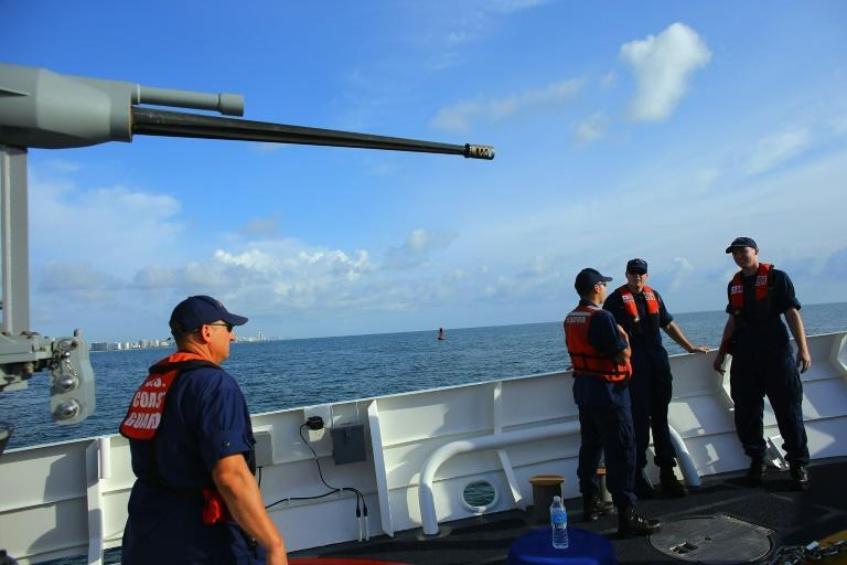 United States Coast Guard personnel stand on the deck of the United States Coast Guard Cutter William Flores on October 17, 2012 just off shore Miami Beach, Florida. The cutter was the third of a planned 58 Fast Response Cutters in the Sentinel Class as the U.S. Coast Guard continues to replace its aging fleet