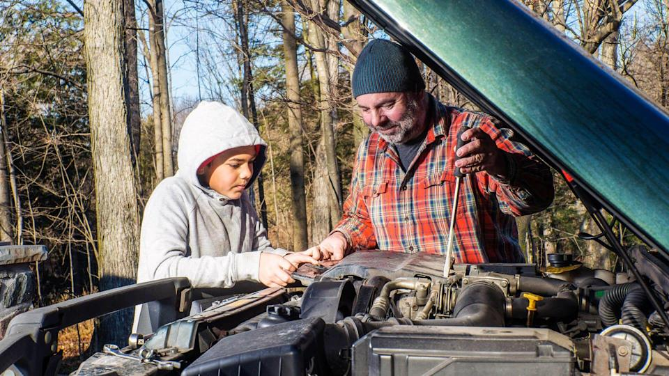 A father teaching his son about vehicle maintenance.