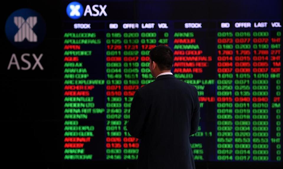 A man looks at the indicator board at the ASX
