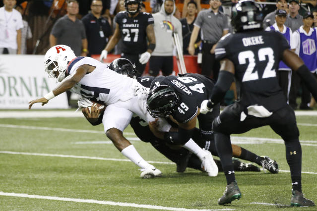 """With no time left in the fourth quarter, Hawaii defensive back <a class=""""link rapid-noclick-resp"""" href=""""/ncaaf/players/270082/"""" data-ylk=""""slk:Kalen Hicks"""">Kalen Hicks</a> (3) and defensive lineman <a class=""""link rapid-noclick-resp"""" href=""""/ncaaf/players/252442/"""" data-ylk=""""slk:Manly Williams"""">Manly Williams</a> (49) tackle Arizona quarterback <a class=""""link rapid-noclick-resp"""" href=""""/ncaaf/players/263219/"""" data-ylk=""""slk:Khalil Tate"""">Khalil Tate</a> (14) just short of the end zone. (AP Photo/Marco Garcia)"""