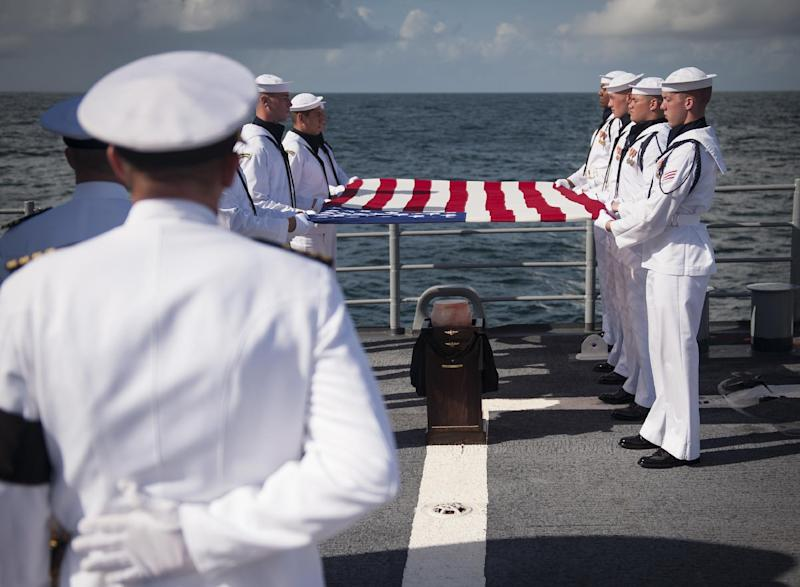 Members of the U.S. Navy ceremonial guard hold an American flag over the remains of Apollo 11 astronaut Neil Armstrong during a burial at sea service aboard the USS Philippine Sea (CG 58), Friday, Sept. 14, 2012, in the Atlantic Ocean. Armstrong, who died last month in Ohio at age 82, walked on the moon in July 1969. (AP Photo/NASA, Bill Ingalls)