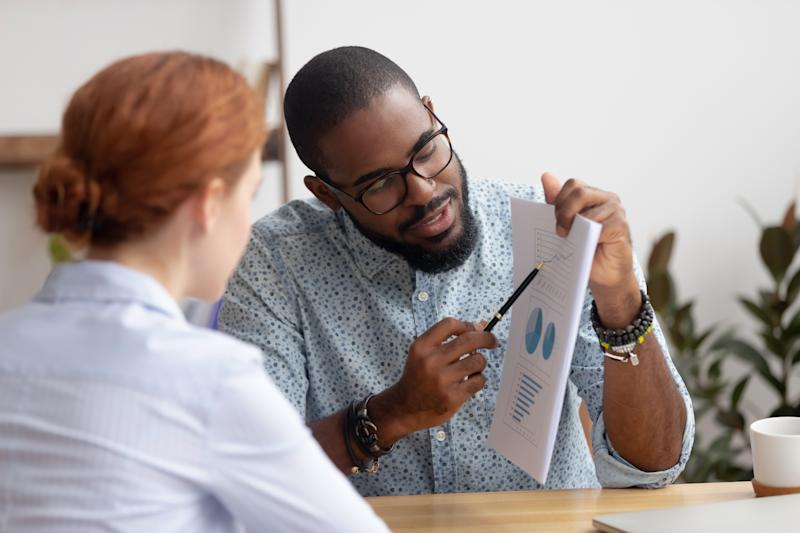 Male black coworker showing document with project results talking to caucasian female colleague. Diverse businesspeople analyzing consulting discussing project results in charts and graphs in office