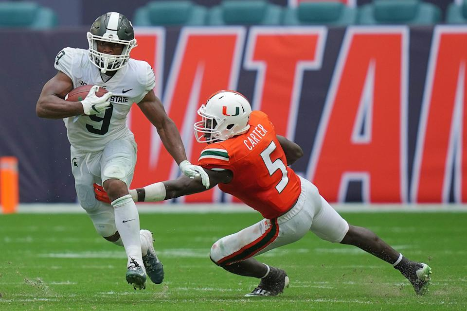 Michigan State Spartans running back Kenneth Walker III runs the ball past Miami Hurricanes safety Amari Carter during the second half in Miami Gardens, Fla. on Sept. 18, 2021.