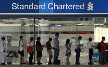 People queue up outside a Standard Chartered Bank branch before operation hours at the central business district in Singapore