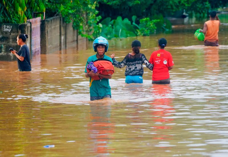 A man wearing a helmet carries his goods through the water in an area affected by floods after heavy rains in Dili