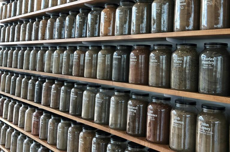 The Equal Justice Initiative collaborates with local communities in Montgomery, Alabama to gather soil at lynching sites to be displayed in glass jars with the victims' names (AFP/Robert CHIARITO)