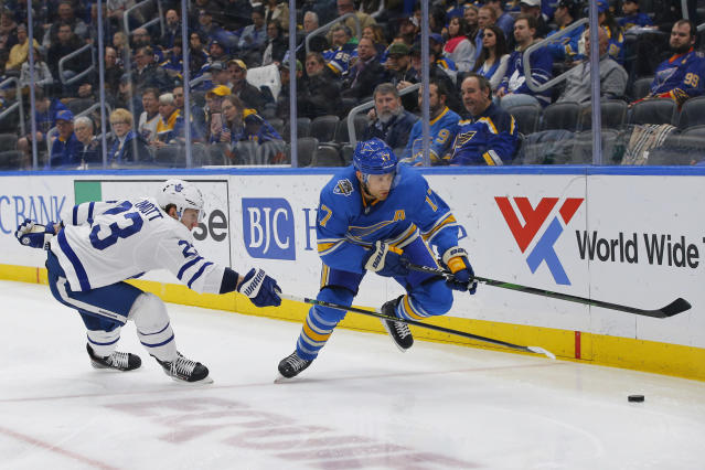 St. Louis Blues' Jaden Schwartz, right, reaches for a loose puck as he is pressured by Toronto Maple Leafs' Travis Dermott during the second period of an NHL hockey game Saturday, Dec. 7, 2019, in St. Louis. (AP Photo/Billy Hurst)