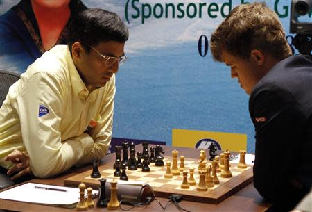 India's Viswanathan Anand (L) plays against Norway's Magnus Carlsen during the FIDE World Chess Championship in the southern Indian city of Chennai November 22, 2013. REUTERS/Babu