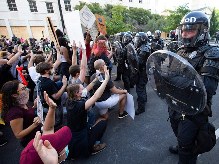 Demonstrators kneel as police officers in riot gear push back, outside of the White House, June 1, 2020 in Washington D.C., during a protest over the death of George Floyd.