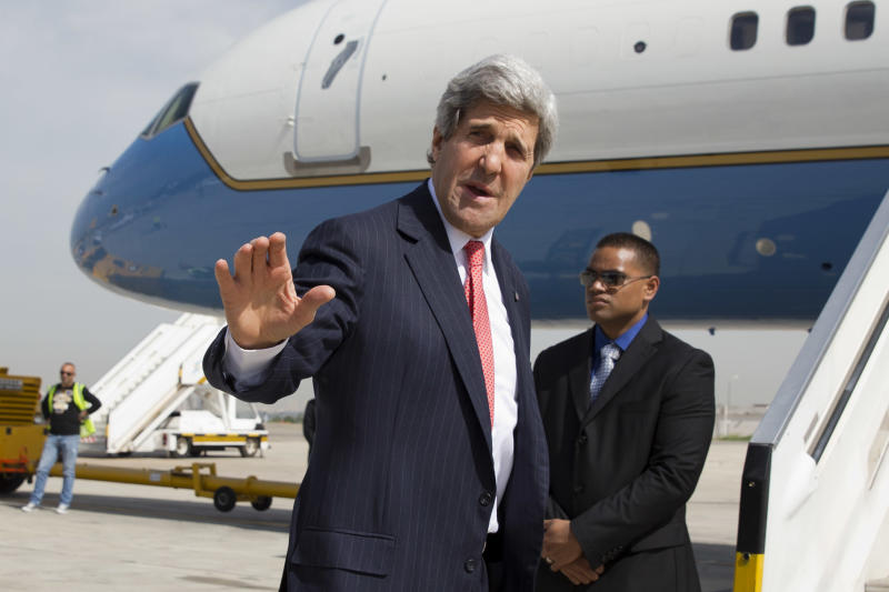 In this April 1, 2014, photo, U.S. Secretary of State John Kerry says goodbye as he leaves Tel Aviv, Israel, continuing on to NATO meetings in Brussels after meeting in Israel with Israeli Prime Minister Benjamin Netanyahu about the Middle East peace process talks. The current trip was to have been a five-day trip to Europe and Saudi Arabia, but with crisis on multiple fronts and Kerry's decision on how to proceed turned a routine trip abroad into a frenetic tour of high-stakes diplomacy marked by abrupt changes in plan that have come to define his 14-month tenure as secretary of state. (AP Photo/Jacquelyn Martin, Pool)