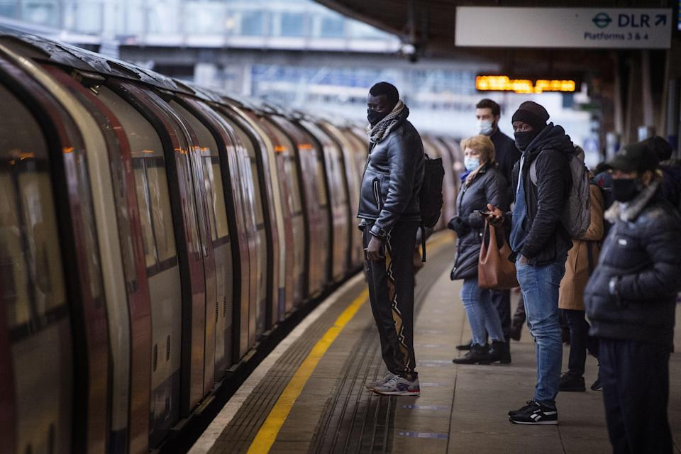 Commuters getting on a Jubilee Line Underground train at Canning Town station during the morning rush hour in London, as England's third national lockdown to curb the spread of coronavirus continues (Victoria Jones/PA) (PA Archive)